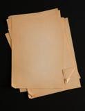 Pilha de folhas velha do papel do ofício isolada no fundo preto Imagem de Stock