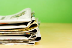 Pilha de jornais na cor no fundo verde Imagem de Stock