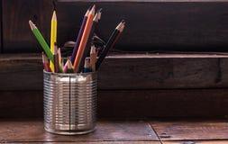 Pilha de lápis coloridos em um zinco de vidro no fundo Fotos de Stock Royalty Free