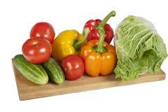 Pilha de legumes frescos na placa de corte de madeira Foto de Stock