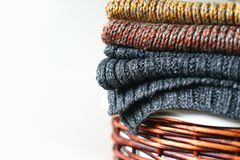 Pilha de lenços feitos malha do inverno na cesta da palha isolada no fundo branco Espaço da cópia gratuita Foto de Stock