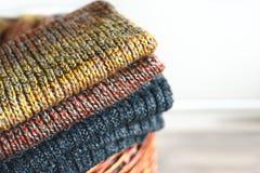 Pilha de lenços feitos malha do inverno na cesta da palha isolada no fundo branco Espaço da cópia gratuita Fotografia de Stock