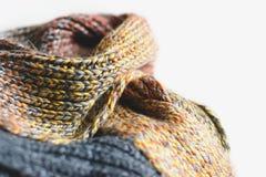 Pilha de lenços feitos malha do inverno na cesta da palha isolada no fundo branco Espaço da cópia gratuita Foto de Stock Royalty Free