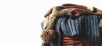 Pilha de lenços feitos malha do inverno na cesta da palha isolada no fundo branco Espaço da cópia gratuita Vista panorâmico Foto de Stock