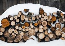 Pilha de lenha nevado no fundo de madeira Imagens de Stock