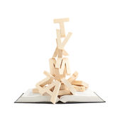 Pilha de letras de madeira sobre o livro Imagens de Stock