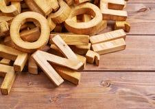 Pilha de letras de madeira sobre a superfície de madeira Fotografia de Stock Royalty Free