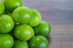 Pilha de limão verde na tabela de madeira Foto de Stock Royalty Free