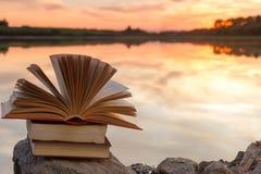 A pilha de livro e o livro encadernado aberto registram no contexto borrado da paisagem da natureza contra o céu do por do sol co