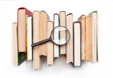 A pilha de livro encadernado registra com a lupa isolada no fundo branco, vista superior Busca para o informatio relevante e nece imagem de stock royalty free