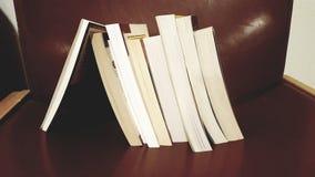 Pilha de livro que inclina-se em um único livro foto de stock