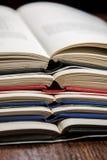 Pilha de livros abertos na tabela de madeira Fotografia de Stock Royalty Free