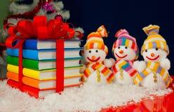Pilha de livros coloridos e de três bonecos de neve Fotografia de Stock