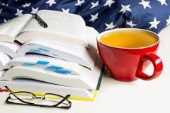 Pilha de livros com marcador, vidros e uma mentira do lápis ao lado de uma caneca vermelha de bebida de tonificação, chá imagens de stock royalty free