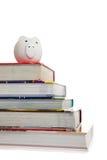 Pilha de livros de texto com um banco piggy branco Imagem de Stock Royalty Free