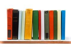 Pilha de livros na prateleira de madeira isolada no branco imagens de stock royalty free