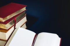 Pilha de livros velhos e de um livro aberto com as páginas vazias vazias contra um escuro - fundo azul imagens de stock royalty free