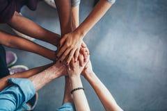 Pilha de mãos que mostram a unidade e os trabalhos de equipa