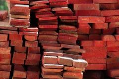 Pilha de madeira empilhada pintada das barras da cor vermelha Materiais de construção imagem de stock