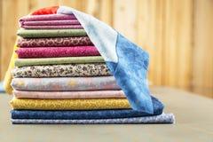 Pilha de material da cópia de algodão da edredão com um bloco na parte superior Fotos de Stock
