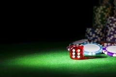 Pilha de microplaquetas de pôquer em uma tabela verde do pôquer do jogo com os dados do pôquer no casino Jogando um jogo com dado Foto de Stock