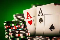 Pilha de microplaquetas e de dois áss na tabela no repes verde Imagens de Stock Royalty Free