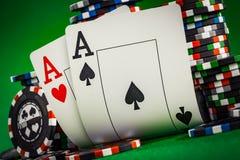 Pilha de microplaquetas e de dois áss na tabela no repes verde Imagem de Stock Royalty Free