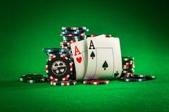 Pilha de microplaquetas e de dois áss na tabela no repes verde Fotografia de Stock Royalty Free