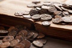Pilha de moedas antigas no livro muito velho Fotos de Stock