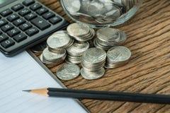 Pilha de moedas com lápis e livro de nota, calculadora na aba de madeira Imagem de Stock