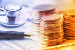 Pilha de moedas com uma pena de fonte e uma caixa-parte de um estetoscópio em uma tabela Imagem de Stock Royalty Free