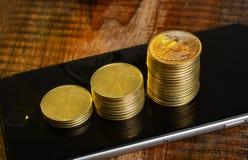 Pilha de moedas da moeda de Bitcoin na tela móvel Imagem de Stock