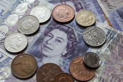 Pilha de moedas de libra em vinte notas da libra Fotografia de Stock