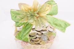 Pilha de moedas de ouro na cesta com fita verde Fotografia de Stock Royalty Free