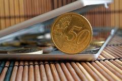 A pilha de moedas do Euro com uma denominação de 50 euro- centavos no espelho reflete mentiras da carteira no fundo de bambu de m Imagens de Stock Royalty Free