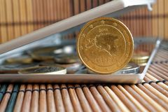 A pilha de moedas do Euro com uma denominação de cinqüênta euro- centavos no espelho reflete mentiras da carteira no fundo de bam Fotos de Stock