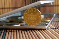 A pilha de moedas do Euro com uma denominação de vinte euro- centavos no espelho reflete mentiras da carteira no fundo de bambu d Fotografia de Stock