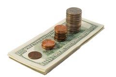 Pilha de moedas e de dólares Fotografia de Stock Royalty Free