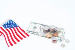Pilha de moedas e de dólares de conta com a bandeira dos EUA no branco, no negócio e em financeiro Fotografia de Stock Royalty Free