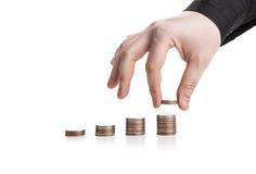 pilha de moedas e de mão humana Fotografia de Stock Royalty Free