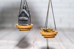 Pilha de moedas e uma casa pequena nas escalas O conceito da escolha, economias do dinheiro e compra de bens imobiliários imagens de stock royalty free
