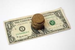 Pilha de moedas em uma boneca ucraniana dos E.U. do papel de cédula um do hryvnia Fotografia de Stock Royalty Free