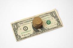 Pilha de moedas em uma boneca ucraniana dos E.U. do papel de cédula um do hryvnia Fotografia de Stock