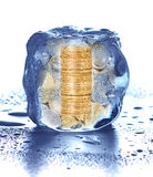 Pilha de moedas no cubo de gelo Foto de Stock Royalty Free