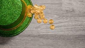 Pilha de moedas de ouro puras dentro da borda do dia verde do St Patricks do chapéu Imagem de Stock Royalty Free
