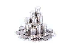 Pilha de moedas que cercam pelas pilhas das moedas isoladas no branco Imagem de Stock