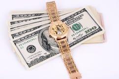 Pilha de 100 notas de dólar e relógios de ouro em um fundo claro Fotos de Stock Royalty Free