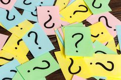 Pilha de notas de papel coloridas com pontos de interrogação no fundo de madeira closeup imagem de stock royalty free