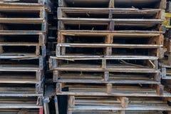 Pilha de páletes de madeira que sentam-se em uma doca de trabalho pronta para o outb Fotos de Stock