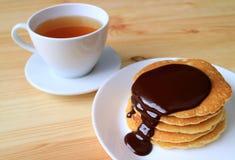Pilha de panquecas com molho de chocolate belga Mouthwatering e um copo do chá quente no fundo foto de stock